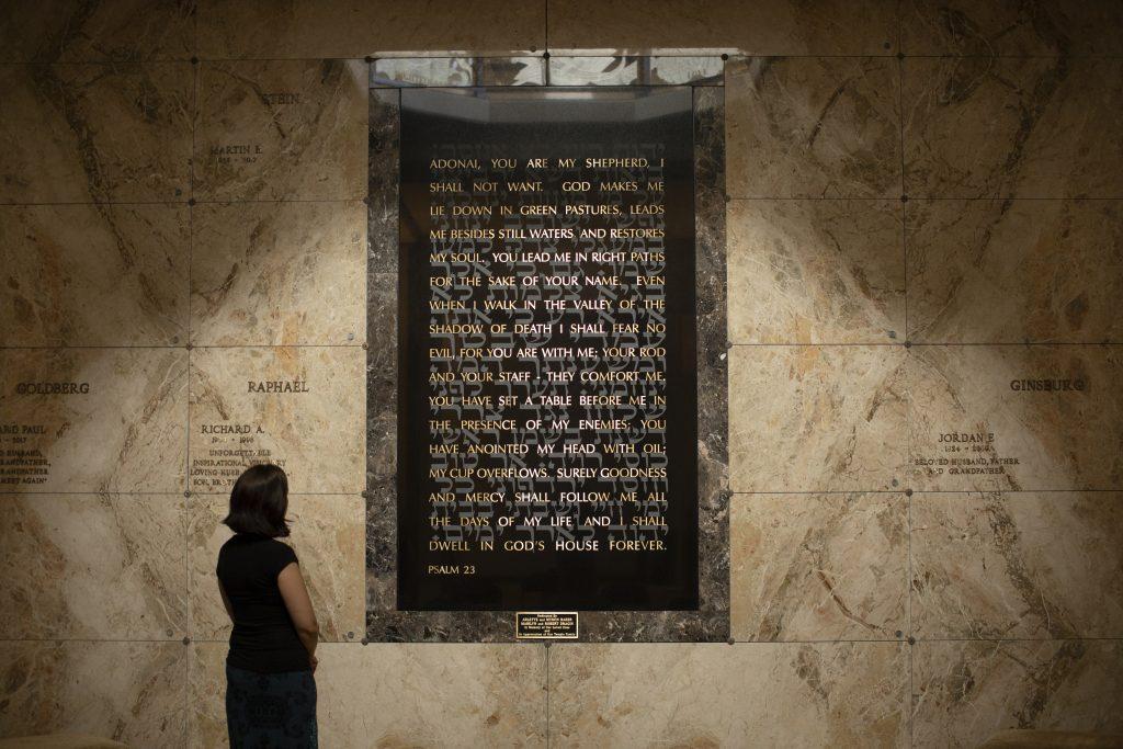 Woman looking at the Twenty-third Psalm artwork at the Beth El Mausoleum